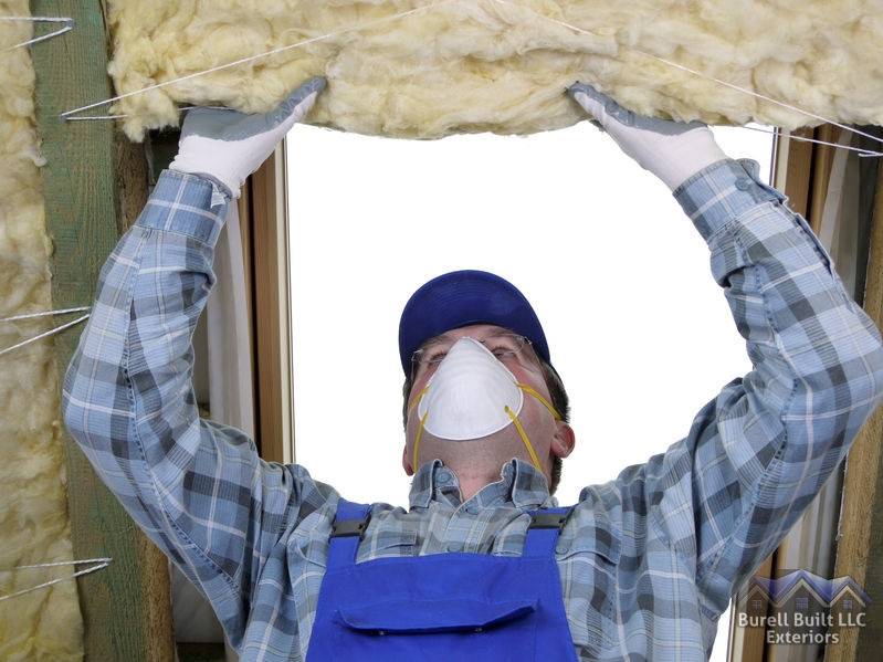 A Picture of a Man Wearing a Mask While Installing Insulation.